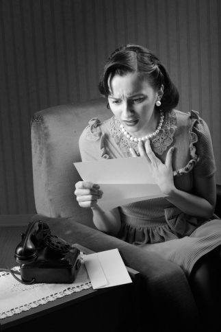 Young woman reading a letter with worried expression