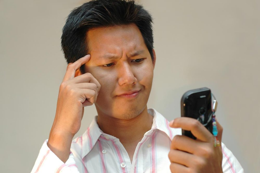 Man-Reading-Text-Message-Confused-Cell-Phone